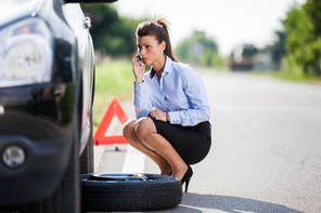 Picture of a woman on her phone on the side of the road needing to change a tire