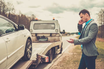 Picture of man on side of the road on his phone who is upset that he is getting his car towed